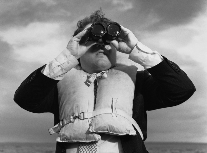 A Businessman searches with a pair fo binoculars